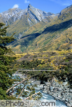 South Island, NEW ZEALAND: A day hiker crosses Matukituki River swing bridge beneath rocky peaks of the Southern Alps. Published in Sierra Magazine, Sierra Club Outings November/December 2002. In 1990, UNESCO honored Te Wahipounamu – South West New Zealand as a World Heritage Area. (© Tom Dempsey / PhotoSeek.com)