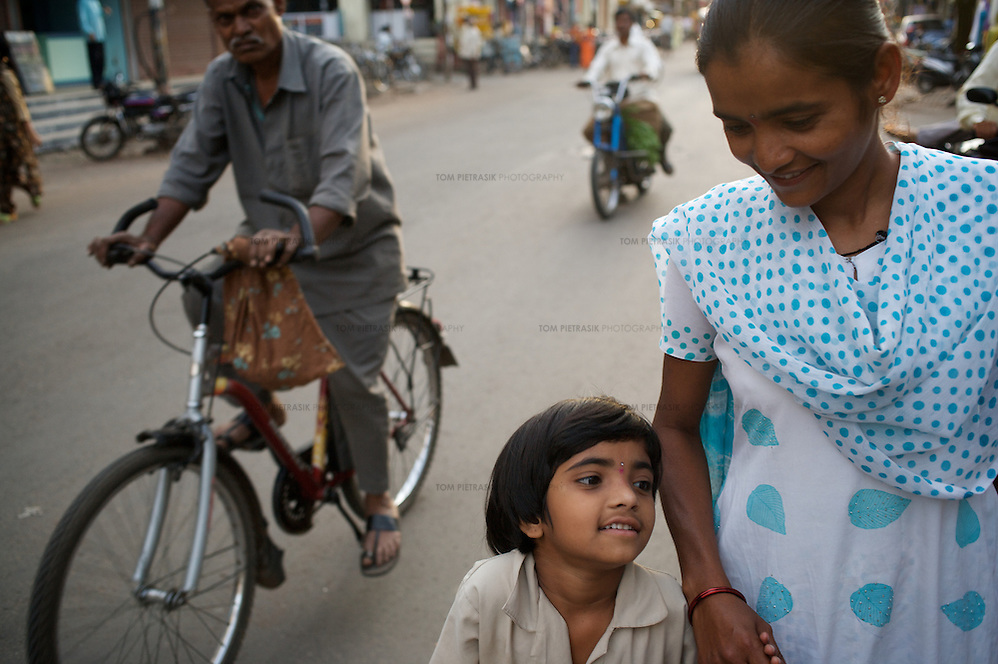 "Vasanti with her youngest daughter Vrinda after collecting her from school in Sangli. ..Like many of the women who work for and with UNDP partners the Save Foundation, Vasanti Shinde only found out that she was HIV positive after her husband became seriously ill with an AIDS-related illness five years ago. Vasanti's husband subsequently died. Vasanti now lives with her two younger daughters Shrudha, age 10, and Vrinda, 8, in the one-room home of her brother in Sangli city. Vasanti's elder daughter, eleven year old Shubhada is being brought up by her paternal grandmother and sees her mother during holidays. Vasanti knows that Shubhada is HIV negative and Shruda is positive but anxiety over the result means that she refuses to have Vrinda tested for HIV. For a monthly income of Rs.3500, Vasanti works as a field officer and counselor for the Save Foundation. She works in the positive-people's pharmacy for no pay. Her work with the Save Foundation entitles her access to a credit union which provides low interest loans covering medical expenses. Though first-line drugs and homeopathic medicine keep Vasanti healthy, she is prone to infection and recently suffered a bout of influenza. Vasanti is completely open about her HIV status and most of her neighbours know that she is HIV positive. Vasanti says that ""I used to feel like I was going to die. Now, because of the Save Foundation, I feel like I'm going to live."" ..Photo: Tom Pietrasik.Sangli, Maharashtra. India.August 27th 2008. (Tom Pietrasik)"