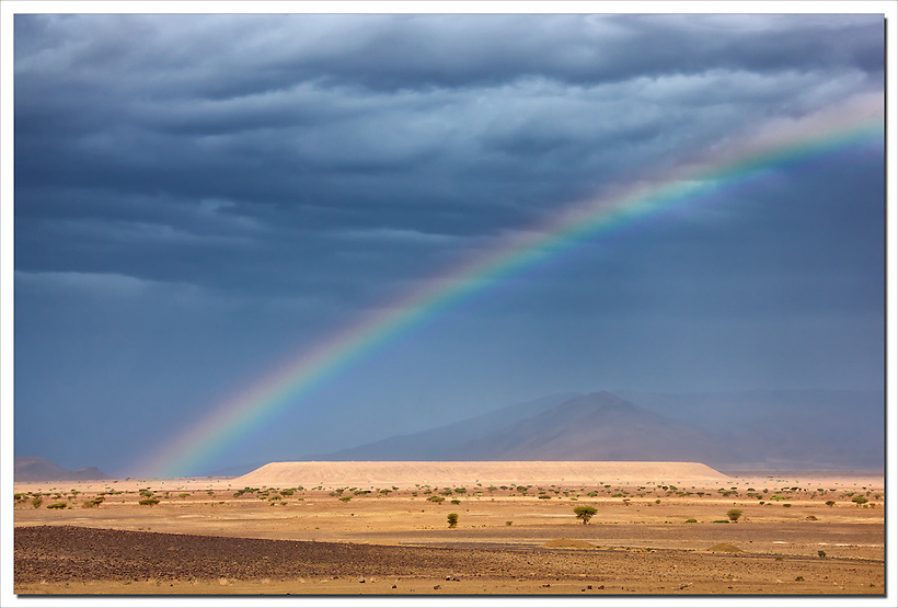 Dark clouds and rainbow in the Sahara desert. (Rosa Frei)