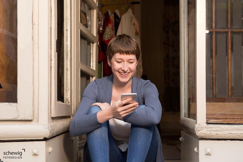 Junge Frau mit Smartphone sitzt im Eingang ihres Geschäftes, Wien, Österreich, Jungunternehmerin, Kreativbereich, Portrait (Dieter Schewig)