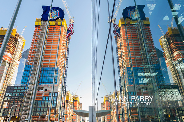 Manhattan, New York, USA. April 12, 2017. Nearby construction at corner or 11th Avenue and W 35th Street is reflected on exterior glass walls of Javits Center on early spring evening. (Ann Parry/Ann Parry, ann-parry.com)
