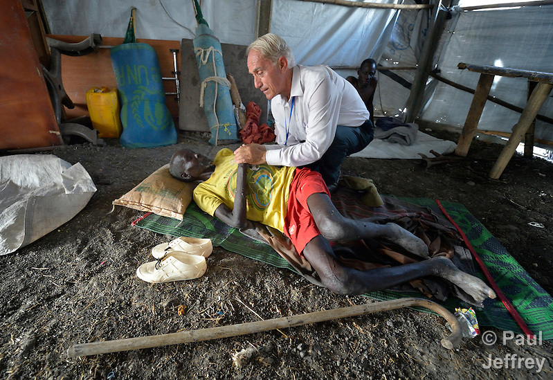 Father Mike Bassano, a Maryknoll priest from the United States, comforts a newly displaced man resting on the floor of a makeshift Catholic chapel inside a United Nations base in Malakal, South Sudan. More than 20,000 civilians have lived inside the base since shortly after the country's civil war broke out in December, 2013, but renewed fighting in 2015 drove another 5,000 people, including this man, into the relative safety of the camp. Bassano lives in the camp to accompany the people there. (Paul Jeffrey)