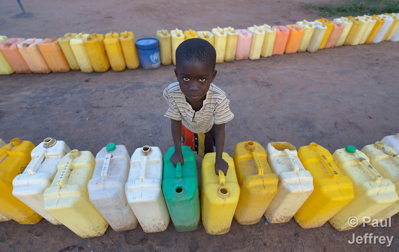 A boy keeps watch on a row of jerry cans before dawn in the Rhino Refugee Camp in northern Uganda. As of April 2017, the camp held almost 87,000 refugees from South Sudan, and more people were arriving daily. About 1.8 million people have fled South Sudan since civil war broke out there at the end of 2013. About 900,000 have sought refuge in Uganda. Because water pumps in the camp are solar-powered, water can only be obtained during daylight hours. Refugees will therefore line up their jerry cans overnight in order to be among the first to get water in the morning. The Global Health Program of the United Methodist Church has supported work to improve access to safe drinking water in the camp. (Paul Jeffrey)