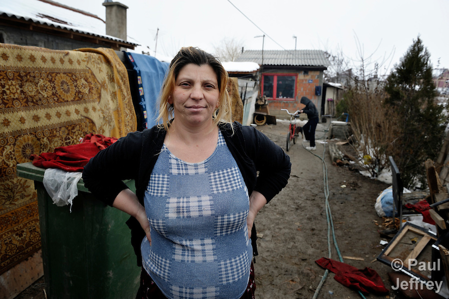 Giltena Duda in front of her home in the Zemun Polje Roma neighborhood of Belgrade, Serbia. Ms. Duda is pregnant with her seventh child. She and her husband are Roma refugees from Kosovo, and thus legally marginalized in Serbia. They built their home on unregistered land and pirate their electrical hookup. Without legal residency, their children can't attend a regular school, and they have difficulties getting formal employment. Yet both participate in an adult literacy program sponsored by the Branko Pesic School, where their children attend classes. The school is supported by Church World Service. (Paul Jeffrey)