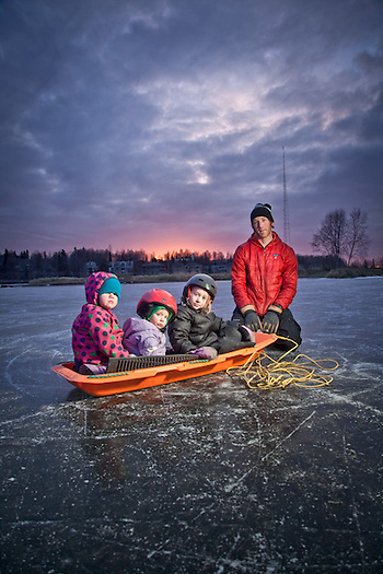 Dayton Young takes a break from pulling his kids, Reese (1), Pipper (4), and their friend Mia (back of sled) on Westchester Lagoon, Anchorage. (Clark James Mishler)