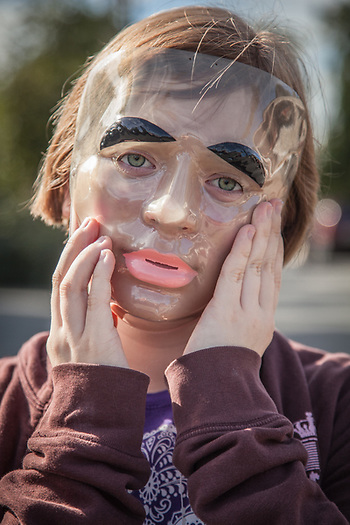 Young girl wearing garage sale mask.  My 12 year old neighbor Julianne Risinger in Anchorage's South Addition neighborhood. (© Clark James Mishler)