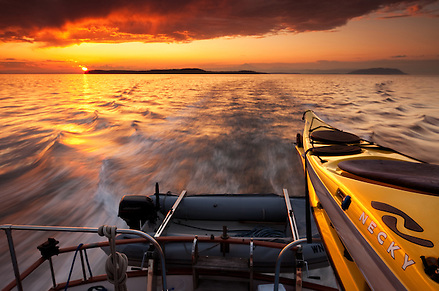 Necky Kayaks mounted on the back of a large boat are lit by the setting sun outside Vancouver Island. (Benjamin Chase / Ben Chase Photography)
