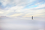A woman walks up a sand dune during sunset at White Sands National Monument, New Mexico. (Seth K Hughes)