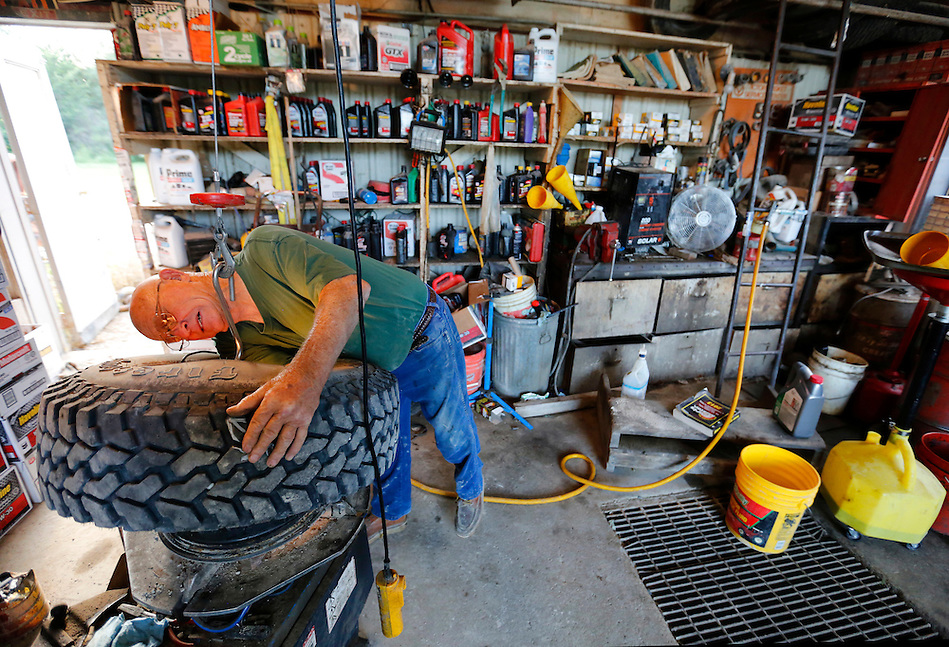 "Frank Eighme, 78, repairs a tire outside in his service station in Arispe.  He has worked in service stations in town for 56 years. ""You gotta have a reason to get out of bed in the morning,"" he says of his passion for the work. (Christopher Gannon/The Register)"