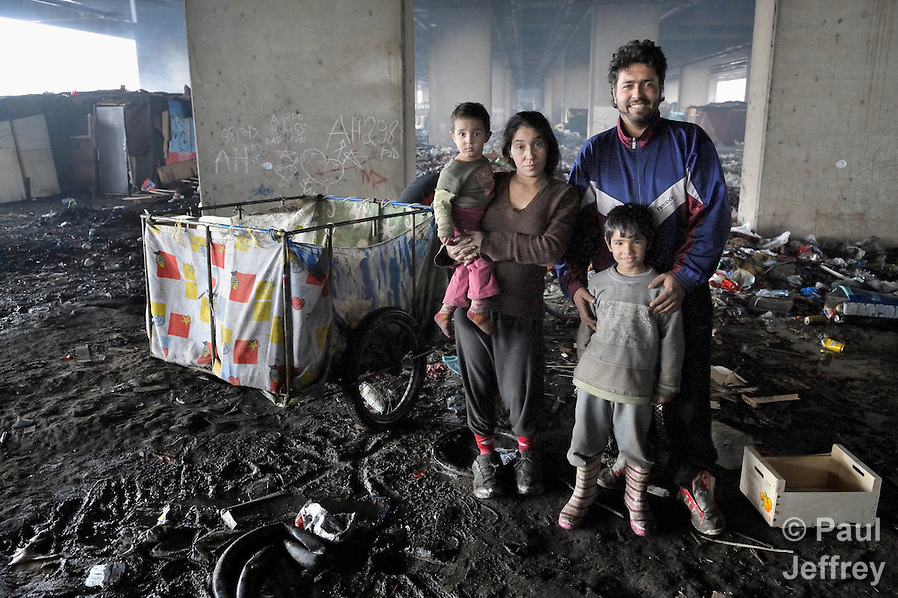 Nevrigda Zitkova and her husband Arden Dasi, with two of their children, lived under a bridge in a Roma settlement in Belgrade, Serbia, when this photo was taken in February 2012. They are refugees from Kosovo. The families that lived here, most of whom survive from recycling cardboard and other materials, were forcibly evicted in April 2012. Many were moved into metal shipping containers on the edge of Belgrade.. (Paul Jeffrey)