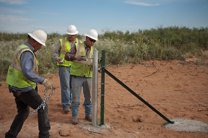 A construction crew works on a gate along the new highway under construction near The Waste Isolation Pilot Plant in Eddy County. WIPP received $172 million as part of the Recovery and Reinvestment Act. The highway will increase access for trucks carrying nuclear waste to the WIPP. (Steven St. John)