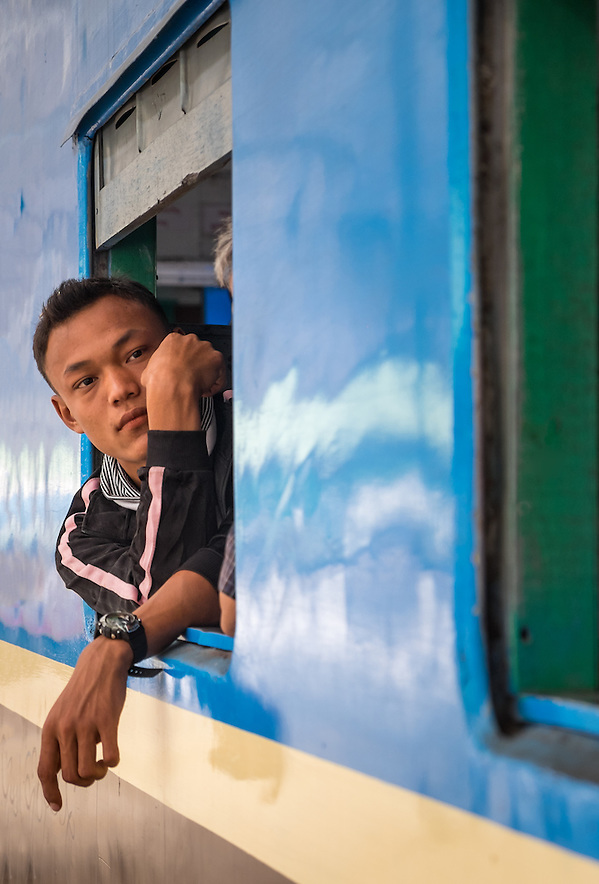 YANGON, MYANMAR - CIRCA DECEMBER 2013: Young burmese man looking away from a train window while it waits for departure in Yangon Central Railway Station (Daniel Korzeniewski)