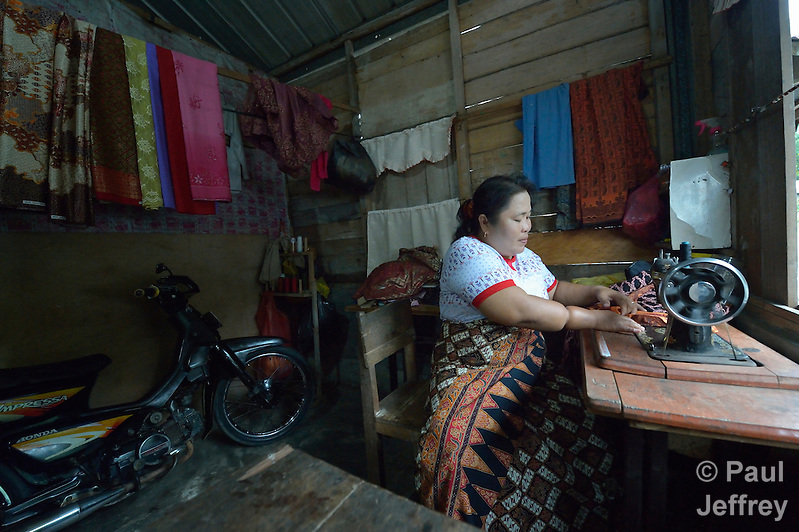 Misbah Teleumbanua sews on a sewing machine in her home in Gamo, a village on the Indonesian island of Nias. Teleumbanua lost one leg as a baby, and spent most of her life hopping around on the other leg. Then following the 2005 earthquake on Nias, a mobile team from YEU, an ACT Alliance member agency, came to her neighborhood looking for people who'd been left disabled by the quake. They told her they'd help her as well. She learned to use crutches and was fitted with a proper prosthesis, then took a three-month tailoring class which allowed her to open her own business sewing clothes for her neighbors. (Paul Jeffrey)