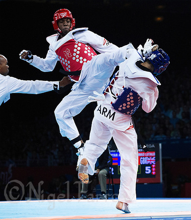 10 AUG 2012 - LONDON, GBR - Lutalo Muhammad (GBR) (left) of Great Britain lands a kick on the head of Arman Yeremyan of Armenia during their men's -80kg category bronze medal A contest at the London 2012 Olympic Games Taekwondo at Excel in London, Great Britain (PHOTO (C) 2012 NIGEL FARROW) (NIGEL FARROW/(C) 2012 NIGEL FARROW)