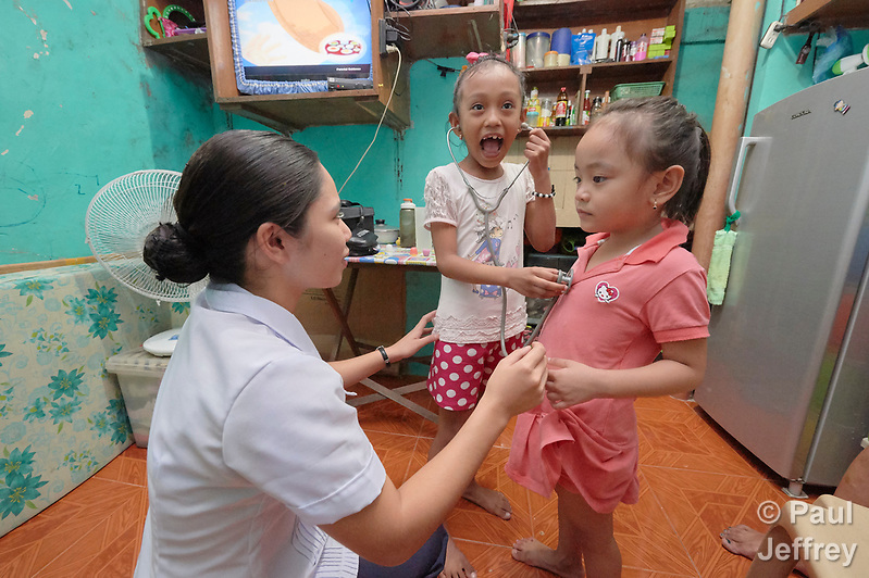Nirish Camporedondo, a student in the Mary Johnston College of Nursing in Manila, helps 5-year old Jean Jamilla Tulauan (center) and her 4-year old sister Jewell Rae hear their heartbeats during a visit to the girls' home in the Parola neighborhood of Manila's Tondo section. Camporedondo and other nursing students regularly visit the neighborhood to do health education and monitor the health of residents. The students also run a feeding program for neighborhood children. The nursing school is supported by United Methodist Women. (Paul Jeffrey)
