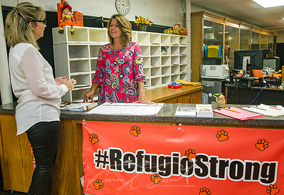 Refugio High School staff members Lisa Herring and Lynette Markert discuss a student as they stand in the school's foyer, which has been temporarily reconfigured to serve as the school office, Oct. 4, 2017, in Refugio, Texas. The town was hard hit by Hurricane Harvey in late August and continues to recover. (Photo by Carmen K. Sisson/Cloudybright)