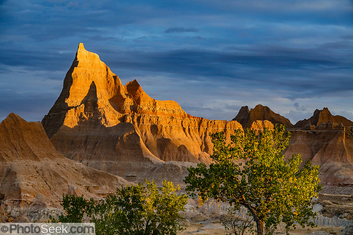 An orange sunrise lights rock formations near Ben Reifel Visitor Center in Badlands National Park, South Dakota, USA.  (© Tom Dempsey / PhotoSeek.com)