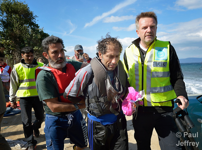 A suspected Turkish migrant smuggler (center) is escorted along a beach near Molyvos, on the Greek island of Lesbos on October 31, 2015. He was rescued from the water after volunteers on the island punctured a raft in which he was trying to flee back to Turkey after depositing a load of refugees. He was turned over to the Greek police. (Paul Jeffrey)