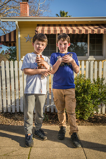"""""""We were going to sell these, but now we think we'll keep 'em.""""  -Eight year old friends Andreas Bjokman and Porter Wild walk home with their 100 year old medicine bottels discovered on the banks of the Napa River near downtown Calistoga. (Clark James Mishler)"""
