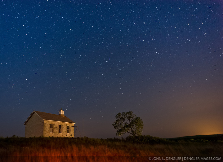 The evening sky reveals stars over the Lower Fox Creek Schoolhouse located in the Tallgrass Prairie National Preserve in the Kansas Flint Hills. The school, on the National Historic Register of Historic Places, was built on land donated by cattleman Stephen F. Jones. Built in 1882, the one-room school had its first classes in 1884. Typical enrollment was between one to 19 students of all grades. The school was closed in 1930 and restored in 1968 by the Garden Clubs in the Mid-East District of Kansas. The glowing light on the right is from the city of Emporia some 20 miles away to the east. The 10,894-acre Tallgrass Prairie National Preserve is located in Chase County near the towns of Strong City and Cottonwood Falls. Less than four percent of the original 140 million acres of tallgrass prairie remains in North America. Most of the remaining tallgrass prairie is in the Flint Hills in Kansas. Tallgrass Prairie National Preserve is the only unit of the National Park Service dedicated to the preservation of the tallgrass prairie ecosystem. The Tallgrass Prairie National Preserve is co-managed with The Nature Conservancy. (John L. Dengler)