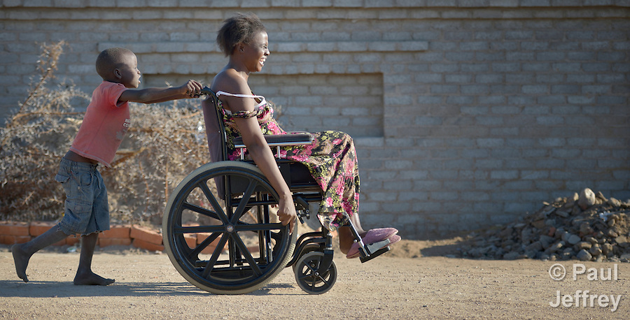 Delina Nleya gets a push from her son Nkosikhona, 7, on the street near their house in Bulawayo, Zimbabwe. Nleya suffered a spinal cord injury and uses a wheelchair provided by the Jairos Jiri Association with support from CBM-US. (Paul Jeffrey)