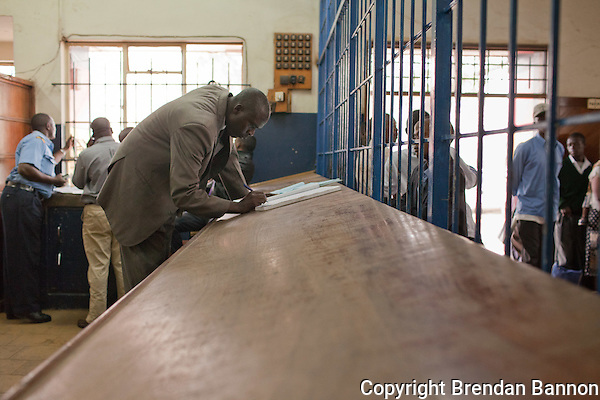 Detective Simiyu signing  aprisoner out of  the holding cells to conduct an interrogation. (Photographer: Brendan Bannon)