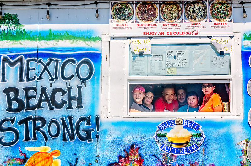 "Employees gather at a window beside a ""Mexico Beach Strong"" mural at Crazy Beach Pizza, Sept. 27, 2019, in Mexico Beach, Florida. The business was damaged by Hurricane Michael in 2018 but is now operating again. (Photo by Carmen K. Sisson/Cloudybright) (Carmen K. Sisson/Cloudybright)"