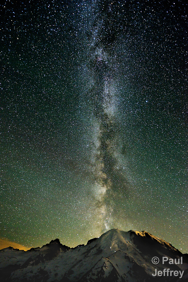 The Milky Way rises above the summit of Mount Tahoma, also known as Mount Rainier, at 2 am on July 25, 2017. The headlamps of climbers can be seen on the slopes of the mountain. The photo was captured during a 30-second exposure. The peaks are located in Mount Rainier National Park in the U.S. State of Washington. Prints of this photo may be ordered at http://langleyumc.photoshelter.com/index/I0000dRy5p3eenmg (Paul Jeffrey)