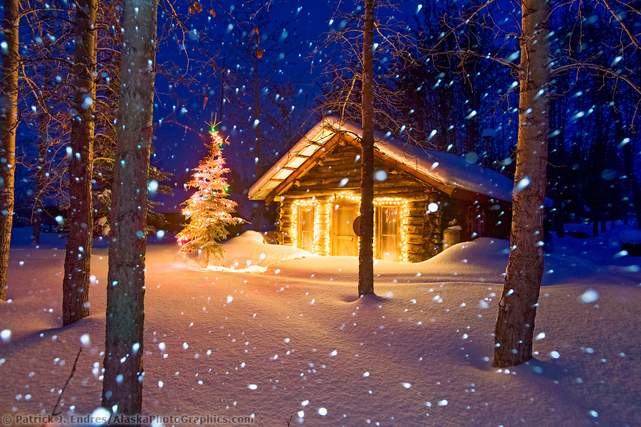 Winter scene of heavy falling snow and a historic log cabin with christmas lights in Wiseman, Alaska (Patrick J. Endres / AlaskaPhotoGraphics.com)