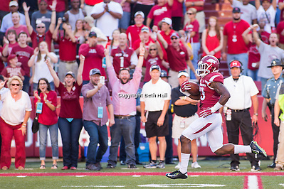 Sep 20, 2014; Fayetteville, AR, USA; Arkansas Razorbacks running back Korliss Marshall (33) returns the opening kick for a touchdown as linebacker Josh Williams (42) looks to block and Northern Illinois University Huskies cornerback Mayomi Olootu (5) and wide receiver Skyler Monaghan (38) pursue during the first half of a game at Donald W. Reynolds Razorback Stadium. Arkansas defeated NIU 52-14. Mandatory Credit: Beth Hall-USA TODAY Sports (Beth Hall/Beth Hall-USA TODAY Sports)
