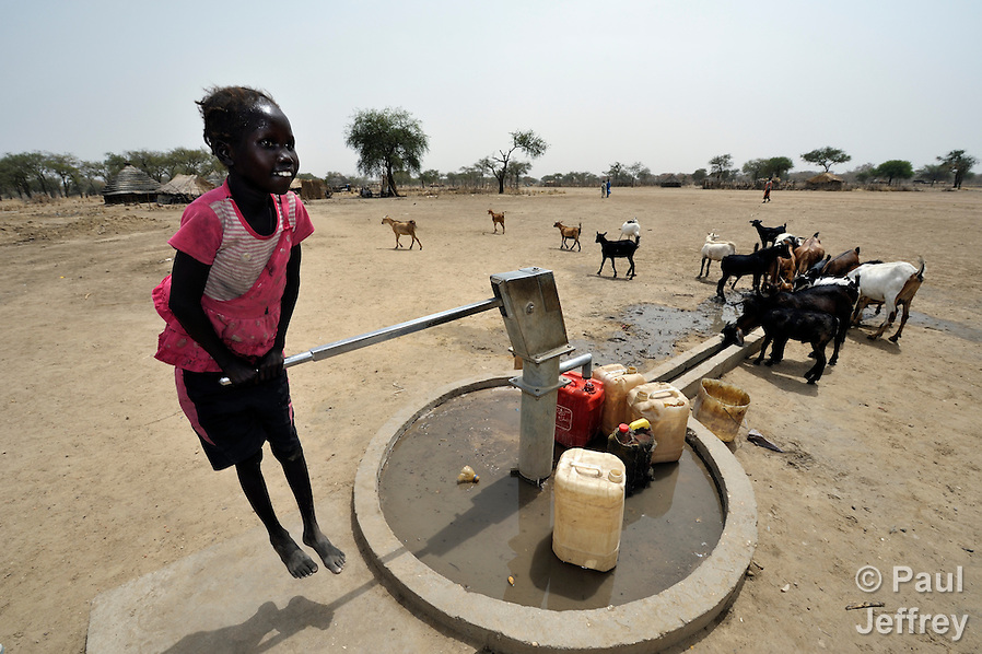 A girl pumps water from a well provided by the Catholic Church in Leu, a village in the contested Abyei region along the border between Sudan and South Sudan. The village was looted and burned in 2011 when soldiers and militias from the northern Republic of Sudan swept through the area, chasing out more than 100,000 Dinka Ngok residents. A few thousand families have returned since northern combatants withdrew in 2012, yet their life is precarious. In Leu, the church rehabilitated a clinic and drilled this well. For political and logistical reasons, the Catholic Church is one of the few organizations willing to openly accompany the people of Abyei during these uncertain times. (Paul Jeffrey)