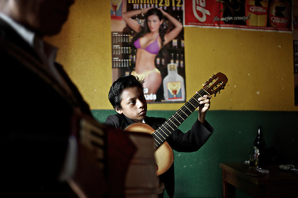 Based on Cristian's testimony, he learned to play the guitar in just three short months.  With his new craft he can now contribute to his domestic economy.  ..Bar La Copa, 3a Calle Poniente #27, La Antigua, Guatemala. ..Según declara Cristian, en tan sólo tres meses ha aprendido a tocar la guitarra.  Con el dominio de este oficio puede ahora contribuir a la economía doméstica. (Martin Herrera Soler)
