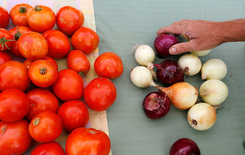Denny Wimmer sets out onions and tomatoes while setting up for the Valley Junction farmers market on July 31, 2014.  Wimmer sells at three markets each week. (Christopher Gannon/The Register)