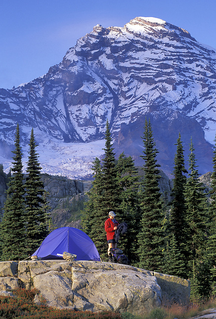Woman setting up tent below Mount Rainier, Mount Rainier National Park, Washington (Brad Mitchell/Brad Mitchell Photography)