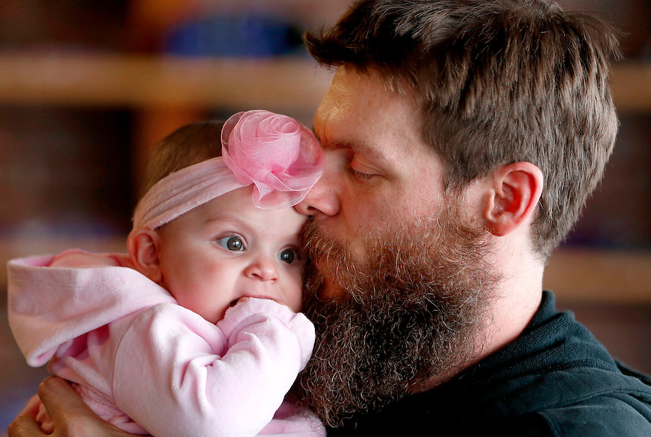 Nate Yoho snuggles his five-month old daughter, Caralyn, while taking a break from work at his Crossfit studio on Merle Hay Road in Des Moines.   Caralyn was born from a surrogate mother.  Nate's wife, Laura, died of brain cancer shortly before her birth. (Christopher Gannon/The Register)