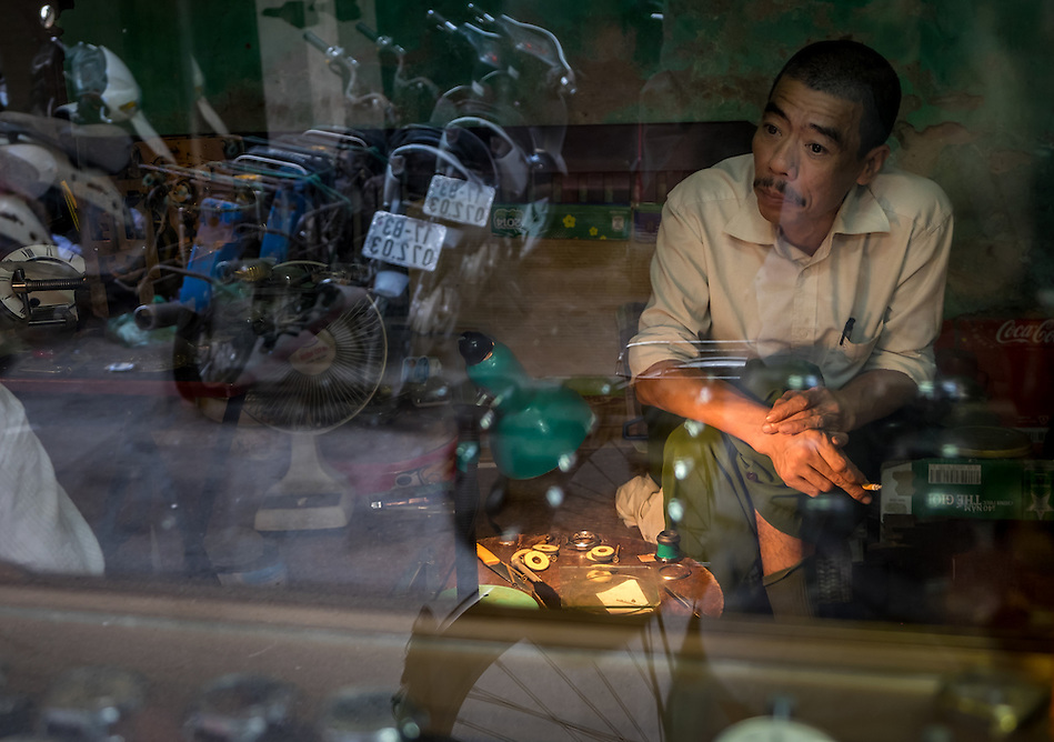 HANOI, VIETNAM - CIRCA SEPTEMBER 2014:  Portrait of Vietnamese man through the window of his shop in the traditional Old Quarter in Hanoi, Vietnam. (Daniel Korzeniewski)