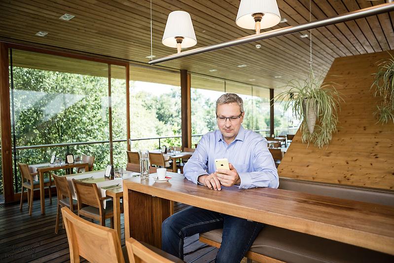 Österreich, Geschäftsmann mit Smartphone bei Kaffeepause an Theke in Restaurant, Casual Look (dieter schewig)