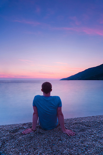 Tourist watching the sunset at Zlatni Rat Beach, Bol, Brac Island, Dalmatian Coast, Croatia, Europe. This photo shows a tourist sitting on Zlatni Rat Beach to watch the sunset. Zlatni Rat Beach is the most popular tourist spot on Brac Island and is a short twenty minute walk from Bol Town. It is famous for being a few hundred metre long spit that protrudes into the Adriatic Sea. It is awesome during the day, but even more awesome at sunset, as the crowds of tourists leave.