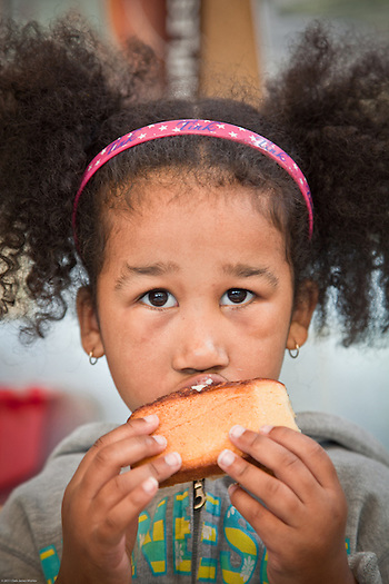 Alana, age 5, enjoys a cinnimon bun at City Market, Anchorage (Clark James Mishler)