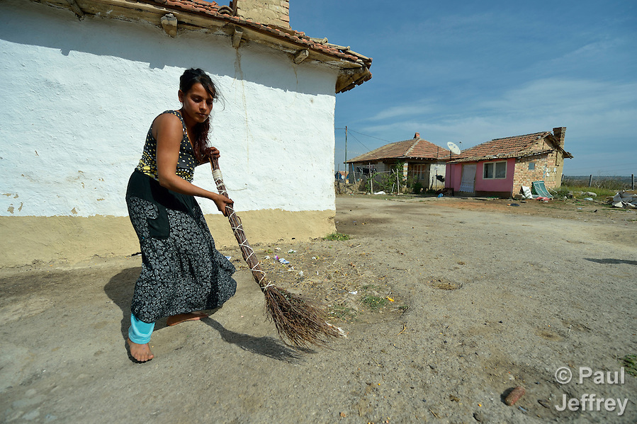 Pepa Adre, 25, sweeps the ground around her home in a largely Roma, Turkish-speaking neighborhood of Dobrich, in the northeast of Bulgaria. (Paul Jeffrey)