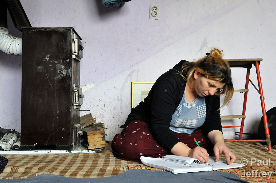 Giltena Duda studies for her basic literacy class in her home in the Zemun Polje Roma neighborhood of Belgrade, Serbia. Ms. Duda is pregnant with her seventh child. She and her husband are Roma refugees from Kosovo, and thus legally marginalized in Serbia. They built their home on unregistered land and pirate their electrical hookup. Without legal residency, their children can't attend a regular school, and they have difficulties getting formal employment. Yet both adults participate in a literacy program sponsored by the Branko Pesic School, where their children attend classes. The school is supported by Church World Service. (Paul Jeffrey)