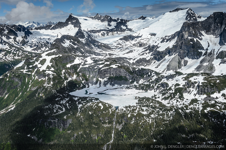 Connelly Lake (center) is a 90-acre alpine lake near Haines, Alaska that drains into the Chilkoot River. Connelly Lake (formerly known as Upper Chilkoot Lake) is the focus of a proposed $32 million, 12-megawatt hydroelectric project by Alaska Power and Telephone Company (AP&T). AP&T proposes to build a dam at the outlet of Connelly Lake that would create a 160-acre reservoir and a 6,200-foot-long penstock down the side of the mountain where water would be delivered to two turbine generators located in a powerhouse near the Chilkoot River into which the lake water would be discharged. Some of the main features of the proposed Connelly Lake project (for example portions of the penstock, the powerhouse, access roads, and the transmission line) would be located in the Alaska Chilkat Bald Eagle Preserve and the Haines State Forest. Environmental concerns include the impact construction and project operation would have on fish spawning and rearing habitat (water turbidity issues), and bald eagles. The eagles rely on the salmon that use the Chilkoot Valley in the fall and early winter when they are attracted to late spawning salmon runs. AP&T wants to build the project to replace the undersea cable that supplies Haines with electricity from Skagway. This photo of the ice and snow covered Connelly Lake was taken in mid-July. (John L. Dengler)
