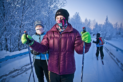 Sisters, Bella and Jordyn Block, out for a cross country ski on a very cold afternoon, as the sun sets behind frosted trees on the coastal trail near Westchester Lagoon, Anchorage (Clark James Mishler)