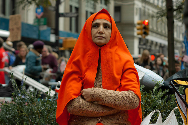 Woman sitting as passersby take pictures during the Occupy Wall Street demonstration in Zuccotti Park. October 21, 2011 (Emon Hassan)