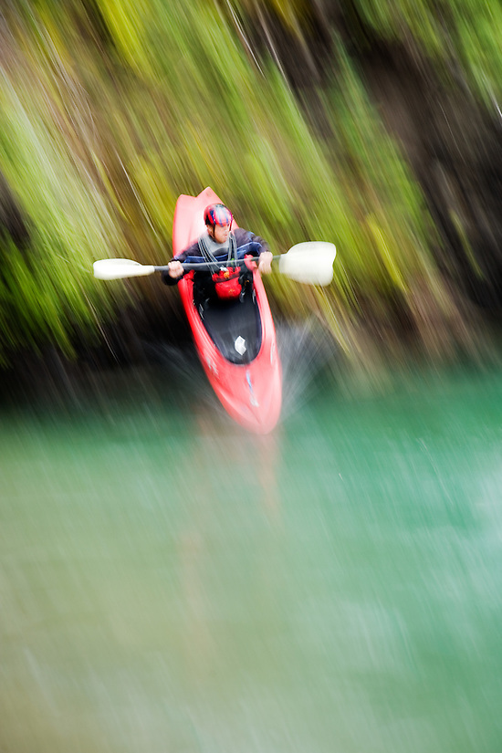 Male whitewater kayaker seal launches into the Kananaskis River just upstream from Widow Maker rapid, Kananaskis County, Alberta, Canada (Brad Mitchell)