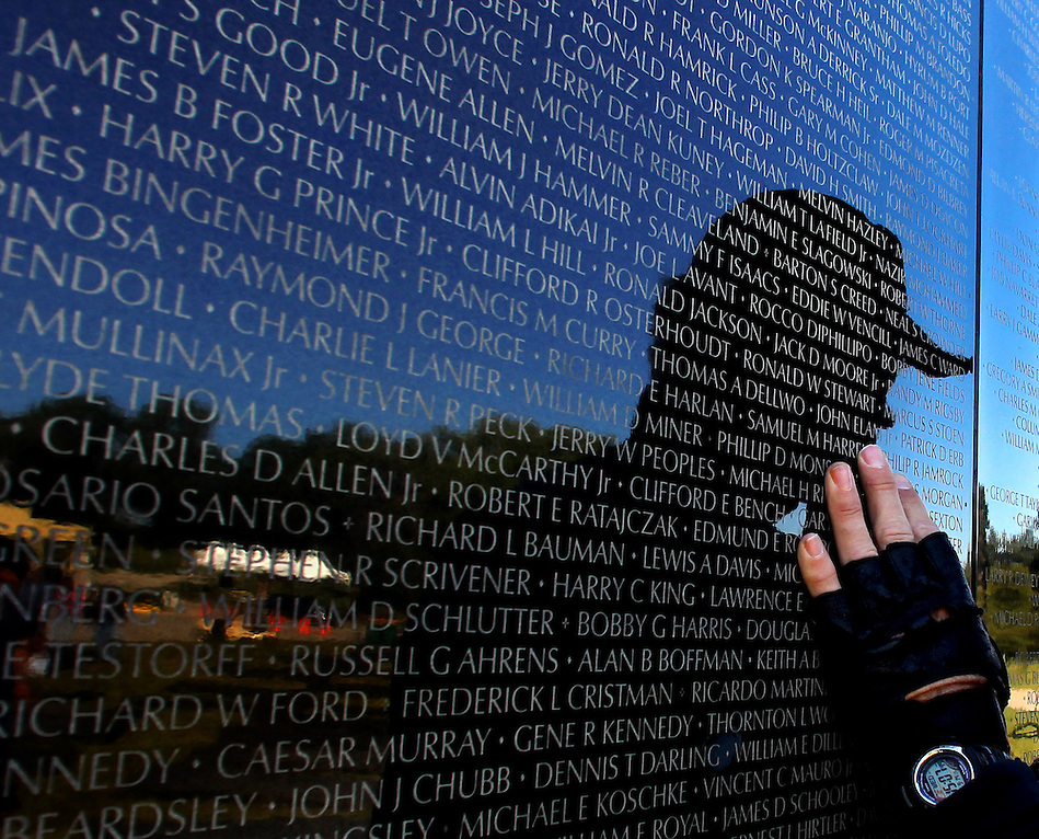 A veteran touches a panel bearing names of those killed or missing in the Vietnam War during assembly of The Dignity Memorial Vietnam Experience in West Des Moines this week. The display, a traveling, three-quarter-scale replica of the Vietnam Veterans Memorial in Washington, D.C., will be open to school children on Thursday and to the public at  from Friday to Sunday. The faux-granite replica is 240 feet long, eight feet high and contains the names of more than 58,000 Americans who died or are missing in Vietnam. More than 30,000 people are expected to see the display while it is in West Des Moines.  (Christopher Gannon/The Des Moines Register) (Christopher Gannon/The Register)