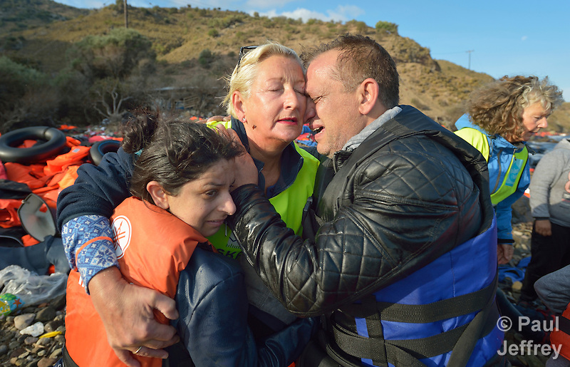 Lisbeth Svendsen, a volunteer from Norway, gets a hug from Nabil Minas as she hugs his wife and daughter on a beach near Molyvos, on the Greek island of Lesbos, on October 30, 2015. The Syrian refugees were on a boat that traveled to Lesbos from Turkey, provided by Turkish traffickers to whom the refugees paid huge sums. Svendsen is one of hundreds of volunteers on the island who receive the refugees and provide them with warm clothing and medical care before they continue their journey toward western Europe. When Minas disembarked from the boat, he fell on his face and kissed the ground. A Christian, he crossed himself and covered his face with his hands, weeping with joy. (Paul Jeffrey)
