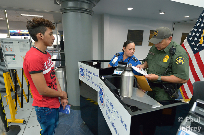 Edwin Chacon, an asylum seeker from Honduras, watches as TSA agent Norma Villegas and Border Patrol agent Rene Perez inspect his papers in the Valley International Airport in Harlingen, Texas. Chacon was transported to the airport by the Posada Providencia in San Benito, where Chacon, 18, stayed for several days after being released by immigration authorities pending a judicial hearing on his asylum request. He was on his way to stay with a relative elsewhere in the United States. Sponsored by the Catholic Sisters of Divine Providence, the Posada Providencia provides a safe place for people in crisis from all over the world who are seeking legal refuge in the United States. (Paul Jeffrey)