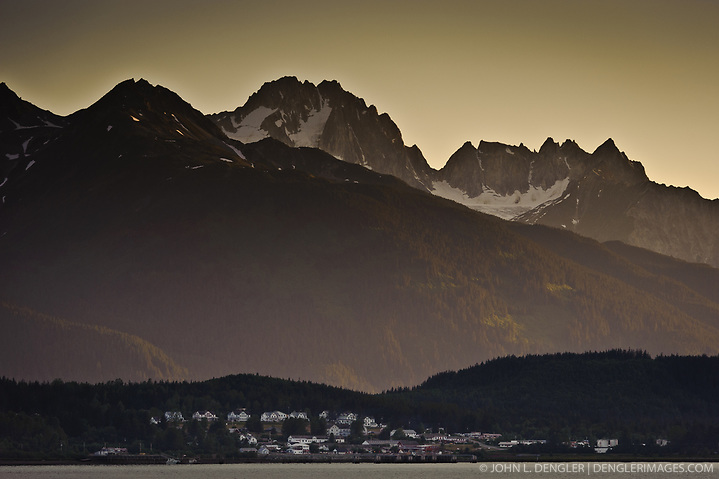 The historic buildings of the former U.S. Army facility, Fort William H. Seward in Haines, Alaska are dwarfed by Mount Emmerich and other peaks of the Takhinsha Mountains as the setting sun lights up the Chilkat River valley. Haines is a cruise ship destination on the Lynn Canal in southeast Alaska. Cruise ships dock at the pictured Port Chilkoot dock near downtown Haines. (John L. Dengler)