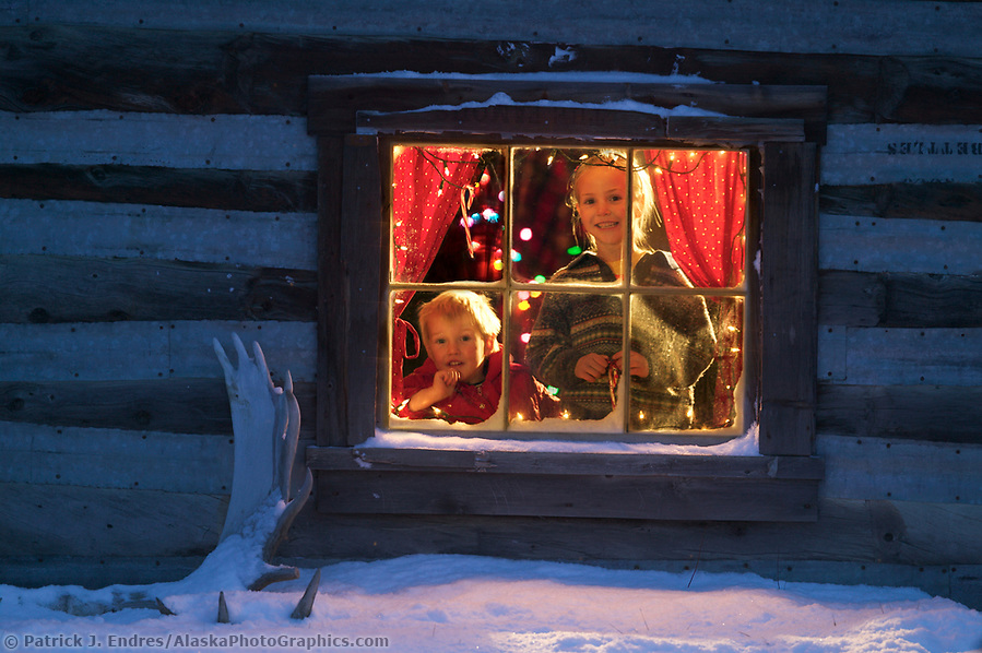 Leo and Julia Hicker peer out of the window of their historic log cabin in winter, Wiseman, Alaska. (Patrick J. Endres / AlaskaPhotoGraphics.com)